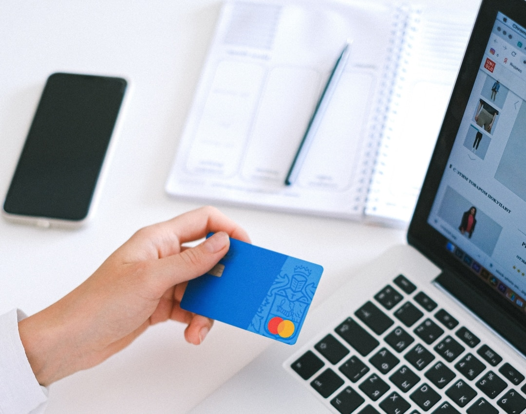 A hand holding a payment card ready to pay for online shopping